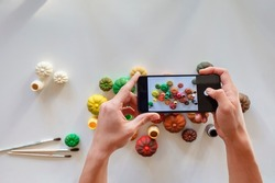 A young man taking a photo of DIY gypsum pumpkins painted in different bright colors of autumn palette to share it in social media, Halloween and Thanksgiving Day ornament, craft decoration, blogger