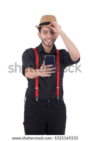A young man taking a selfie holding the tip of the hat he wears and smiling, wearing black clothes and suspenders, isolated on a white background. #1025169235