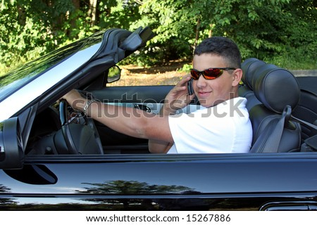 A young man talking on his cell phone and driving at the same time.