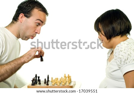 A young man teaching his daughter how to play chess