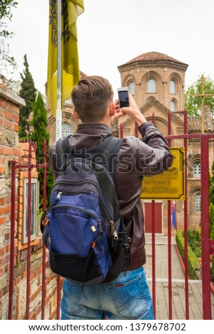 A young man - tourist takes a picture to the smartphone Church of Panagia Chalkeon dedicated to the Virgin Mary in Thessaloniki in spring.