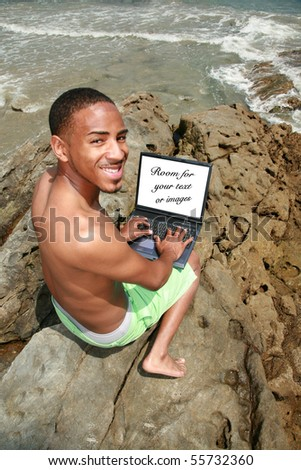 a young man uses his laptop computer while at the beach outdoors