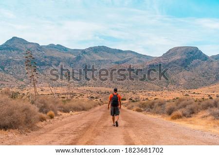 A young man walking along a desert path in the natural park of Cabo de Gata, Nijar, Andalusia. Spain, Mediterranean Sea Stock fotó ©