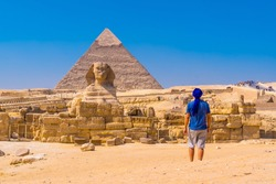 A young man walking towards the Great Sphinx of Giza and in the background the pyramid of Khafre, the pyramids of Giza. Cairo, Egypt
