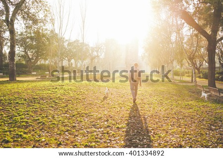 a young man walking with a dogs in the park at sunset
