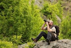 A young man watching birds trought binoculars in the mountain early morning