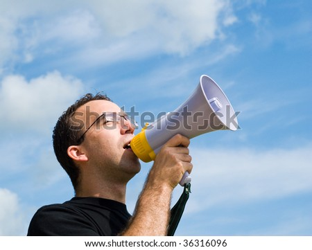 A young man wearing glasses is talking into a megaphone outside with blue sky behind him