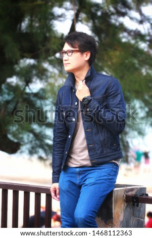 A young man wearing glasses wearing a denim jacket #1468112363