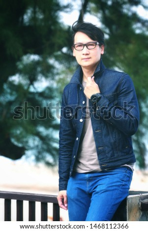 A young man wearing glasses wearing a denim jacket #1468112366