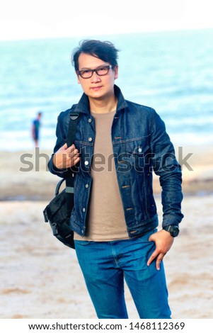 A young man wearing glasses wearing a denim jacket #1468112369