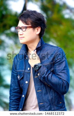 A young man wearing glasses wearing a denim jacket #1468112372