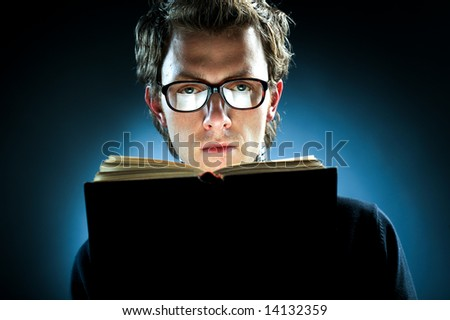 A young man wearing spectacles reading a book