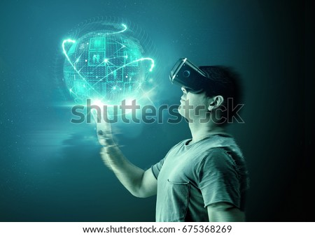 A young man wearing virtual reality (VR) goggles and headset with a projection of a digital world. #675368269