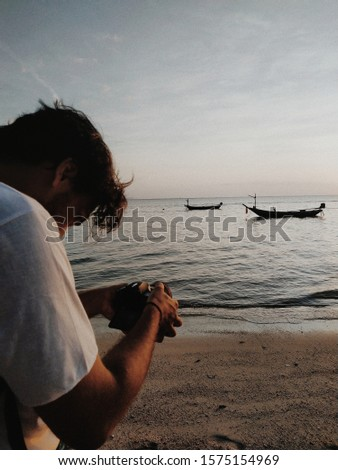 A young man with a camera shoots a video at sunset by the ocean.  A guy is filming a boat at sea in the setting sun.  An operator with a camera in his hands, shooting on vacation, on vacation.