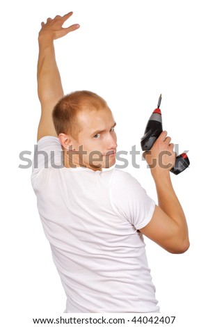A young man with a drilling machine trying to make a hole in the wall, isolated on a white background.