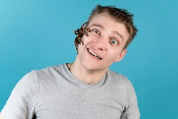 A young man with a huge spider on his face. Fright, shock and surprise