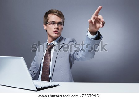 A young man with a laptop clicks on an invisible button