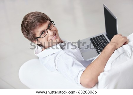 A young man with a laptop on a couch