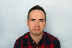 A young man with a sad expression. Frustrated guy. Portrait of a sad man. Portrait of young modern trendy guy against a blue background. Man cry with tears.