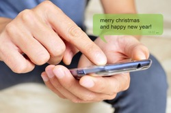 a young man with a smartphone and the text message merry christmas and happy new year in a chat bubble