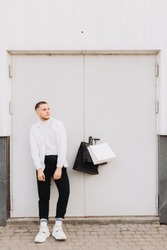 A young man with a stylish haircut and wearing white and black is posing next to the white door somewhere in the street. His shopping bags are hanging on the doorknob
