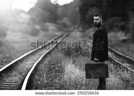 a young man with a suitcase on a railway line black and white photography