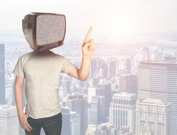 A young man with a vintage TV instead of a head against the backdrop of a metropolis at sunset. Addiction to television. Modern businessman on the background of the city. Obsolescence of business mode