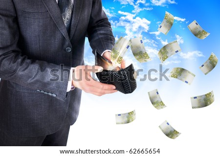 A young man with a wallet from which cash flow ejected