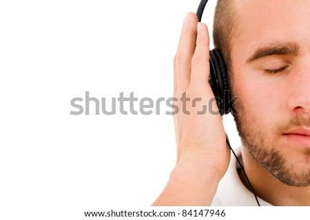 a young man with eyes closed listening to music with headphones, isolated on white