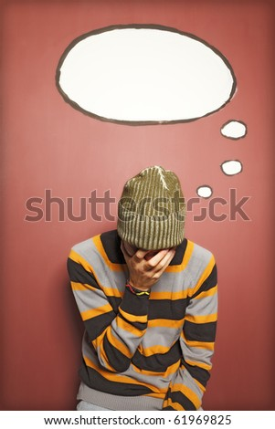 A young man with his face in his palm - thought bubble copy-space