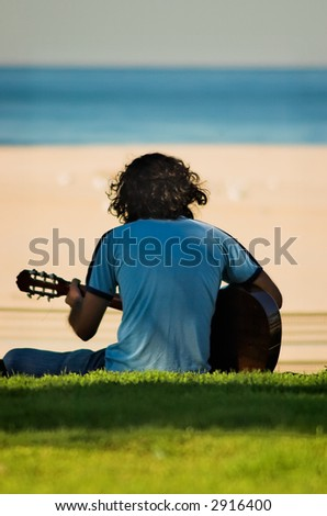 A young man with long curly hair playing his guitar at the beach