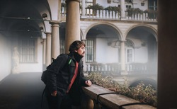 A young man with long hair, a beard and mustache in a gray wool coat, red sweater, jeans and a backpack is waiting on an old balcony with baroque columns.Fog,smoke and dampness.Lviv, Italian courtyard