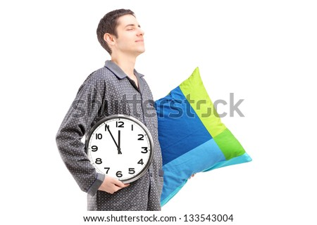 A young man with pillow and clock sleepwalking isolated on white background