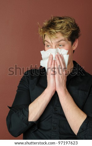 A young man with the flu or allergies blowing his nose