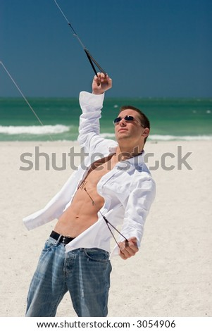A young man working the control lines of a stunt kite on the public beach in Treasure Island, Florida.