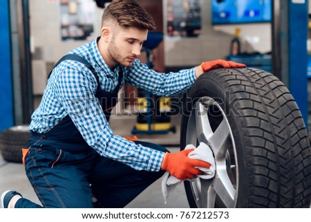 A young man works at a service station. The mechanic is engaged in repairing the car. A young mechanic works with a car wheel. #767212573