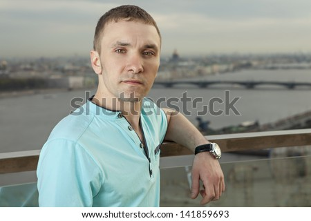 A young man 27 years old, Caucasian, Slav, Russian, dressed in turquoise shirt with short sleeves, horizontal portrait, close-up, against background of panorama of European cities. One person, male.
