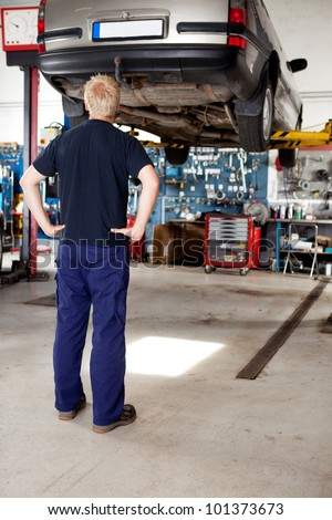 A young mechanic looking at a car that needs repair - stock photo