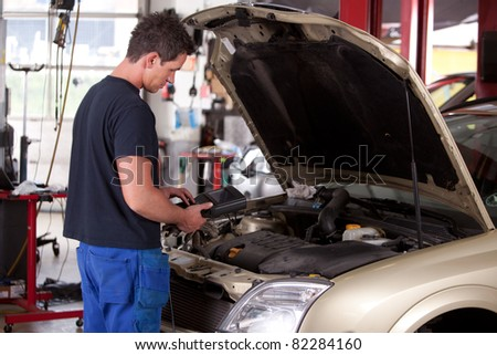 A young mechanic running a diagnostic test on a car