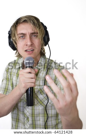 A young mid 20s male sings down radio mic whilst monitoring himself through Headphones. Studion Shot, Shallow depth of field, lots of copyspace with a slightly abstract concept.