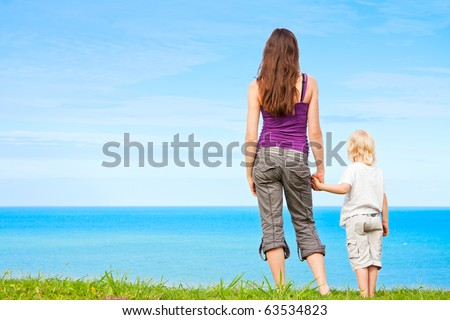 stock photo : A young mother and child holding hands and looking at
