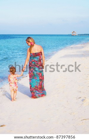 a young mother and her daughter are walking along the beach
