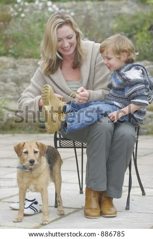 A young mother does up the bootlaces of her son while the family dog looks on