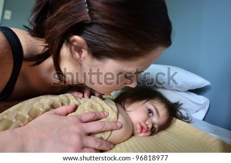 A young mother hugs her baby in bed. Concept photo of motherhood, newborn, baby, relationship, parenting, love ,care.