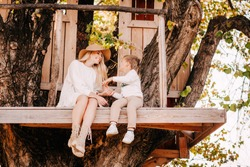 A young mother in a hat and white dress with the son in the tree house