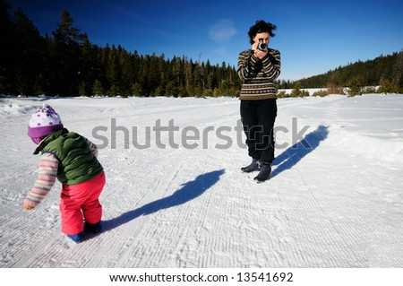 A young mother is filming her two year old daughter playing in the snow at the cross country ski resort in Sierra Nevada mountains in the vicinity of lake Tahoe, California.