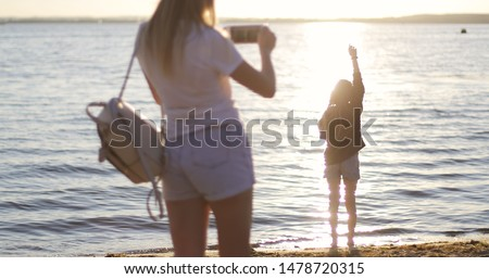 A young mother shoots a daughter on a mobile phone on the background of the sunset. A woman and a cute girl are resting by the lake. Sun kissed child.
