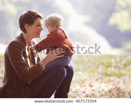 A young mother sitting on the grass holding her baby