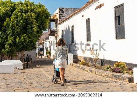 A young mother walking next to the white church of Betancuria, west coast of the island of Fuerteventura, Canary Islands. Spain