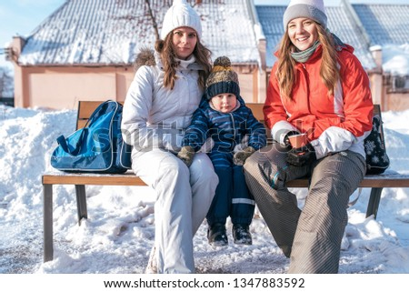 A young mother with young son 4-5 years old, girlfriend are sitting in winter in city, relaxing outdoors after walk, in her hand glass of hot drink, with bags for skates. Rest at weekend in winter.